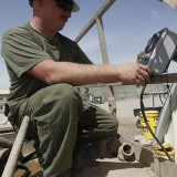 U.S._Marine_Corps_Cpl._Jonathan_M._Klindt,_a_heavy_equipment_mechanic_with_Marine_Wing_Support_Squadron_271,_mounts_a_control_box_onto_a_skid-mounted_hydro_seeder_at_Camp_Leathernec_in_Helmand_province_130401-M-B